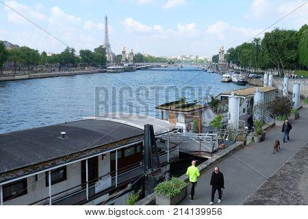 PARIS, FRANCE - APRIL 29, 2017: View of Seine embankment, famous Alexandre III bridge and Eiffel Tower