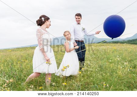 A young cute couple and their daughter in wedding dresses are walking in nature with balloons. The concept of a young happy family and ease in family relationships