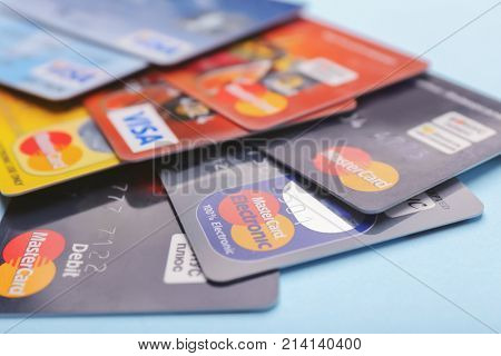 KIEV, UKRAINE - OCTOBER 2, 2017: Different Visa and MasterCard credit cards on color background