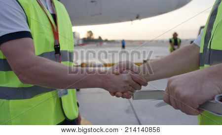 Employees in yellow dickey shake hands. Airport workers shakes hands. Engineers shake hands after checking. Airport workers 4K