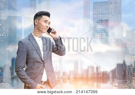 Asian Businessman On Phone In A City