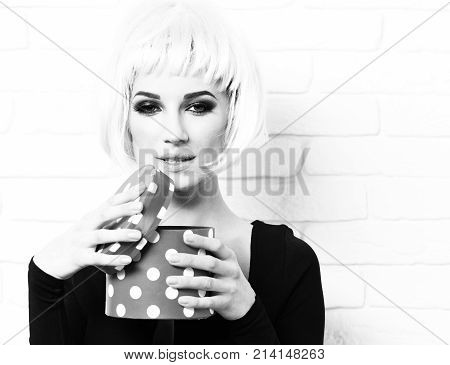 pretty cute sexy girl or beautiful young woman with fashion makeup on satisfied face in pink wig and black dress with deep neckline open red present box on white brick wall background