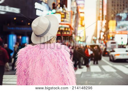 Fashionable tourist woman visiting New York City Time`s Square wearing stylish street style outfit.