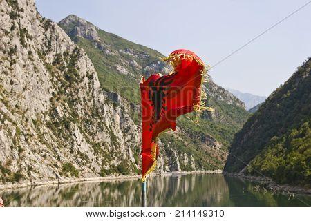 Red albanian national flag on Komani lake