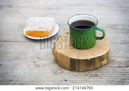 tea with honey on the comb on a wooden table
