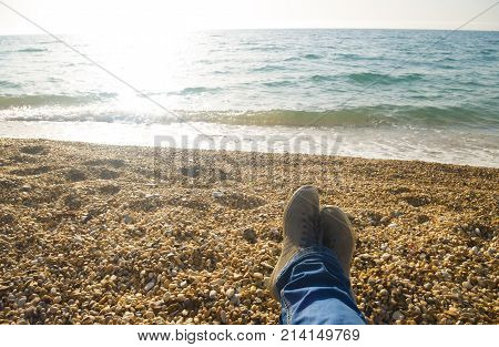 relax on the beach. Men's feet on the beach background