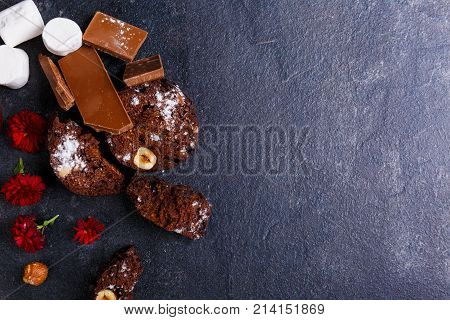 Chocolate cake with hazelnuts, marshmallows, chunks of powder sprinkled with powder