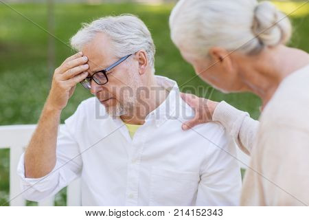 health, stress, old age and people concept - senior man suffering from headache outdoors