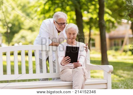 old age, technology and people concept - happy senior couple with tablet pc computer at summer park