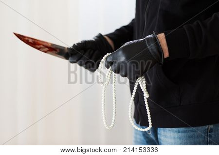 murder, robbery and people concept - close up of criminal or murderer holding knife in blood and pearl jewelry at crime scene