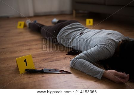 murder, kill and people concept - dead woman body and knife in blood lying on floor at crime scene