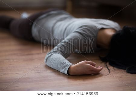 murder, kill and people concept - unconscious or dead woman body lying on floor at crime scene
