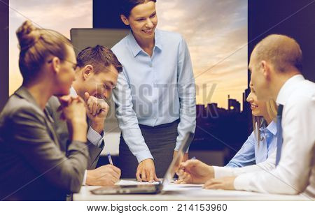 business, deadline and corporate concept - smiling female boss talking to business team at office  over city view background