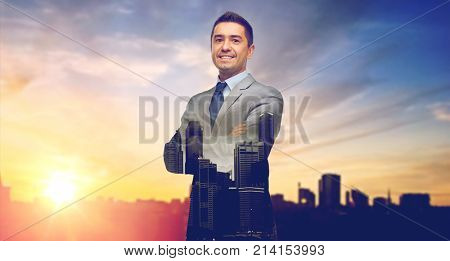 business, people and office concept - happy smiling businessman in suit over city and sun light background and double exposure