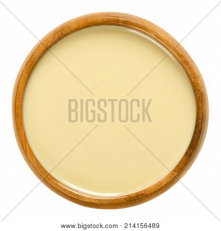 White almond butter in wooden bowl. Smooth food paste made of shelled blanched almonds. Fine puree of the nuts of Prunus dulcis. Isolated macro food photo close up from above on white background.
