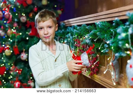 Waiting for present. Pleasant euphoric little boy and holding hand in Christmas stocking while expecting surprise