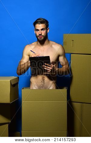 Guy With Naked Torso Counts Boxes. Man With Beard