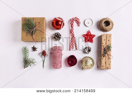 Christmas decoration composition gift box pine cones ball spruce branches candle ribbon candy cane on white festive table isolated. New year winter holiday xmas. Top view flat lay copy space