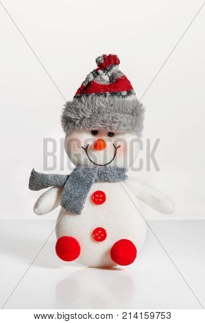 Christmas decoration trinket representing a cute snowman isolated on white background. Snowman in a fur hat and scarf. Studio. Christmas decorations.