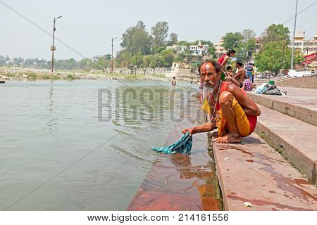 RISHIKESH, INDIA- APRIL 17, 2017: Sadhu washing his clothes in the river Ganges in India