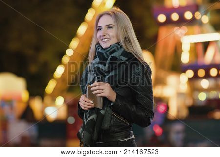 young beautiful woman alone drinks whiskey alcohol from flask. Outdoors at night in an amusement park. Night city background