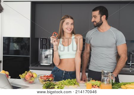 A couple is preparing a salad for breakfast. A man and a woman are posing in the cooking process. A man looks at a girl, a girl looks at the camera and eats something. They are in the modern kitchen.