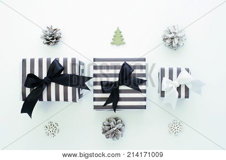 Striped black and white gift boxes, decorative snowflakes, Christmas trees and cones on a laconic white background. The concept for greeting cards, invitations. Top view.