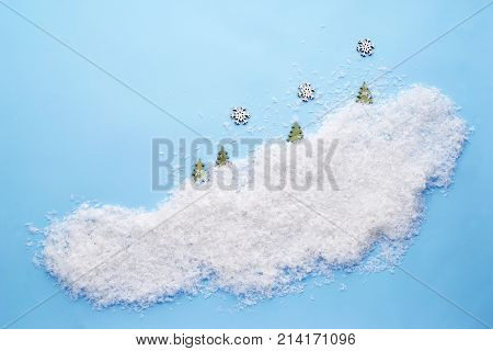 Small snowflakes and Christmas trees on a cloud of decorative snow on a laconic blue background. A template for late postcards, calendars. Top view.
