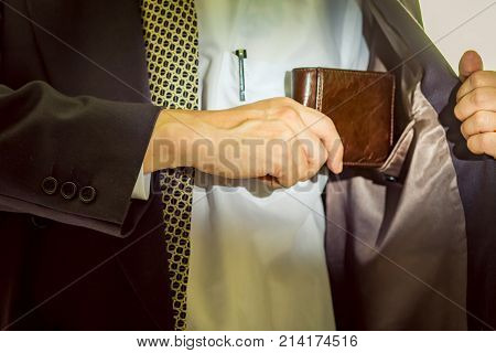 A business man taking out his wallet from suit pocket.