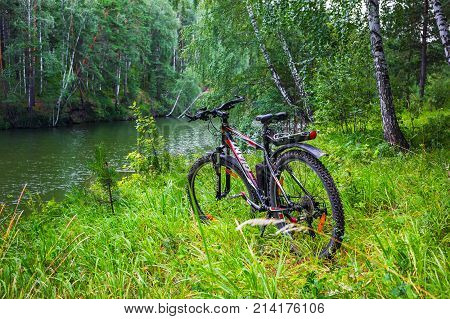 The Separate river (a tributary of the Ob river) in Novosibirsk oblast Siberia Russia - July 21 2017: a mountain bike on the river in the summer