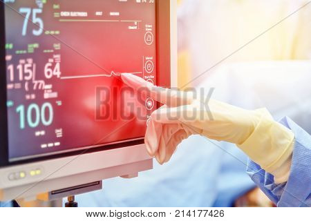doctor hand touch on electrocardiogram showing patient heart rate in emergency room at hospital with blur background