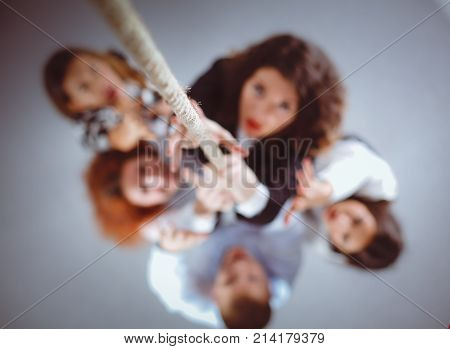 Image of businesspeople ascending up the rope , standing