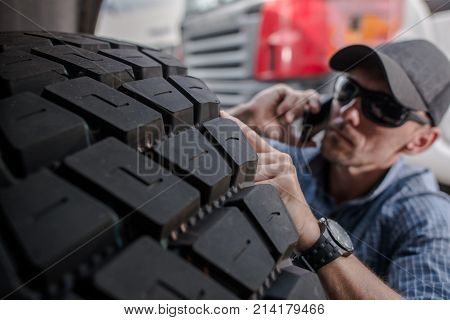 Caucasian Trucker Choosing Truck Tires by Checking the Tread and Talking with His Boss.