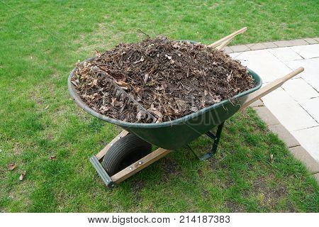garden wheelbarrow filled with dirt and garden waste