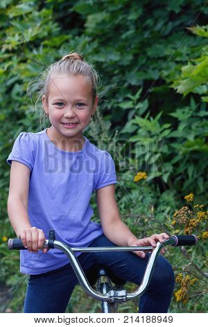 portrait of a little girl sitting on velocipede smiling closeup