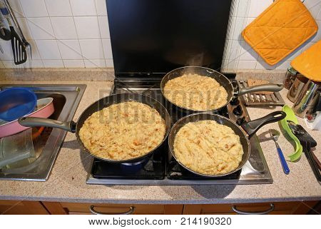 Three Big Pans With The Food Named Frico A Typical Italian Dish