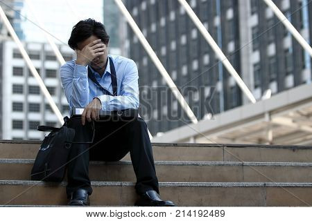 Frustrated stressed young Asian business man feeling tired and exhausted with job