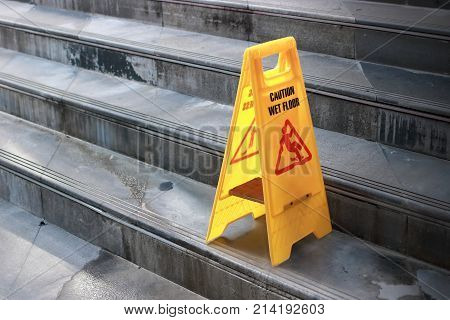 Yellow caution wet floor sign at staircase of outdoor city.