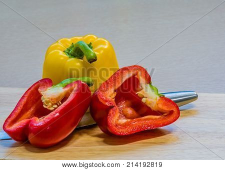 Red Paprika Cut In Half Leaning Against A Yellow Paprika