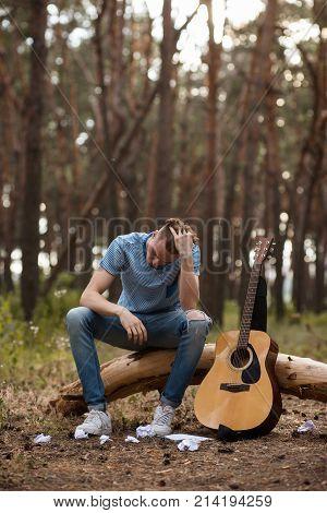 Art complication guitar nature man concept. Working process. A headache from ideas.