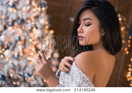 Sexy woman with a glass of champagne. Beautiful girl in a sexy dress. Bright 'N Joyful Christmas!  Asian girl in silver tinsel dress. Warmest Wishes For Christmas!