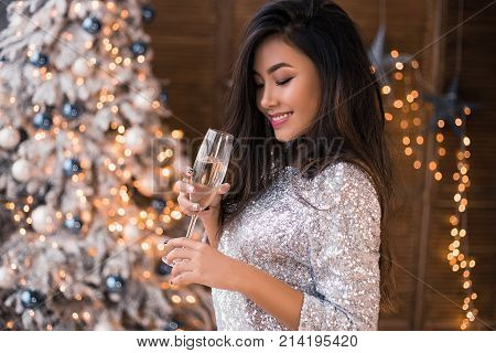 Cheerful asian lady in beautiful dress with a glass of champagne. Sexy smiling. Christmas party. Christmas Eve. X-mas, winter holidays and people concept
