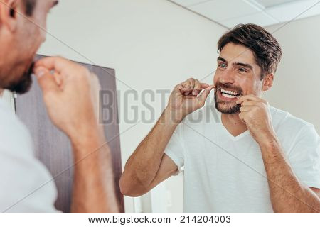 Man looking in the bathroom mirror and using dental floss to clean his teeth. Reflection of man in bathroom mirror while brushing teeth in morning.