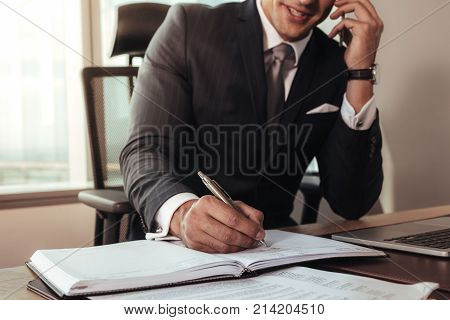 Entrepreneur writing notes sitting at his desk and talking on phone. Young man making business plans and discussing on mobile phone.