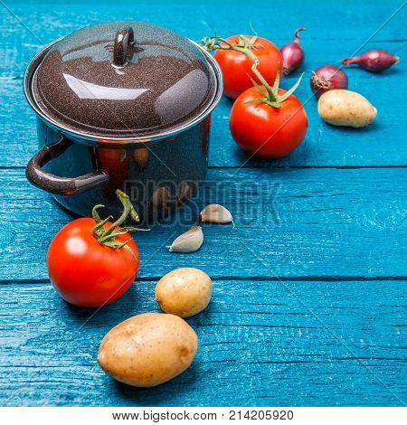 Photo of iron pot for soup, tomato, potatoes, onions on blue wooden background.