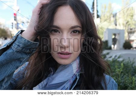 A pretty girl is walking and posing in a windy street. The wind uncurls her nice long brown hair with curls. She is wearing blue denim jacket with scarf.