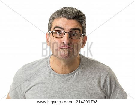 portrait of 40s weird and nerd man on glasses in ridiculous silly and stupid face expression looking at camera isolated on white background in freak and idiot concept