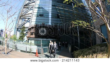 Tokyo, Japan - April 20, 2017: Nippon Television headquarter with Japanese white-collar business workers walking in Shiodome area. Ghibli clock at Nittele Tower in Shinbashi.