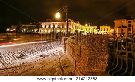 Night time on the historic landmark New Bridge Puente Nuevo of Ronda town in Spain. with running cars across the road and moving people and cars.