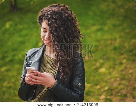 Portrait of relaxed young lady in autumn park reading a text message on mobile phone. Beautiful young african girl with dark curly hair using cell phone, outdoor.
